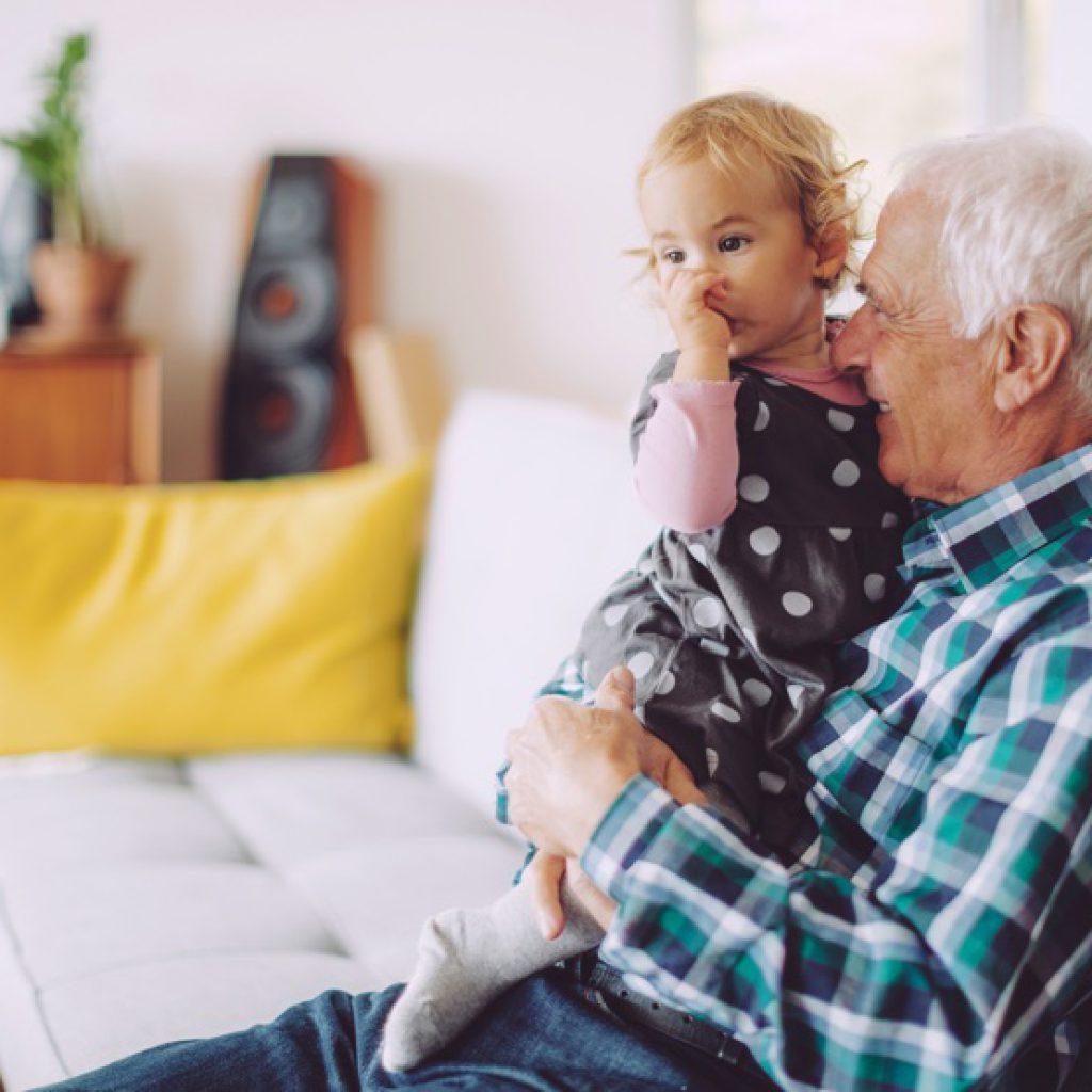 Älterer Mann hält Kleinkind auf dem Arm