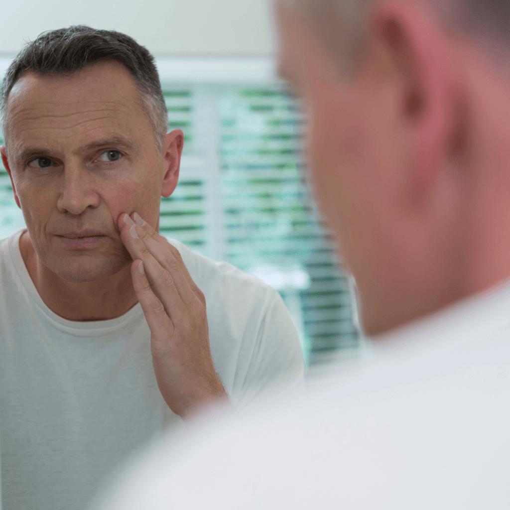 Älterer Mann betrachtet sein Gesicht im Spiegel