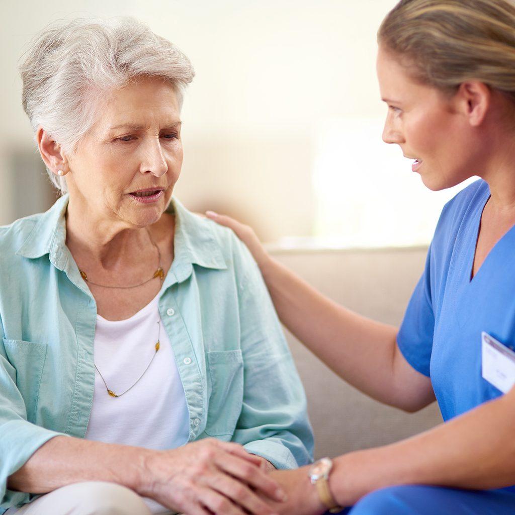 Arzthelferin im Gespräch mit älterer Frau