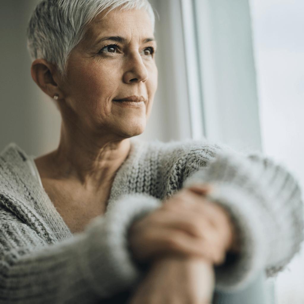 Frau schaut aus dem Fenster und denkt über Auslöser einer hepatischen Enzephalopathie nach