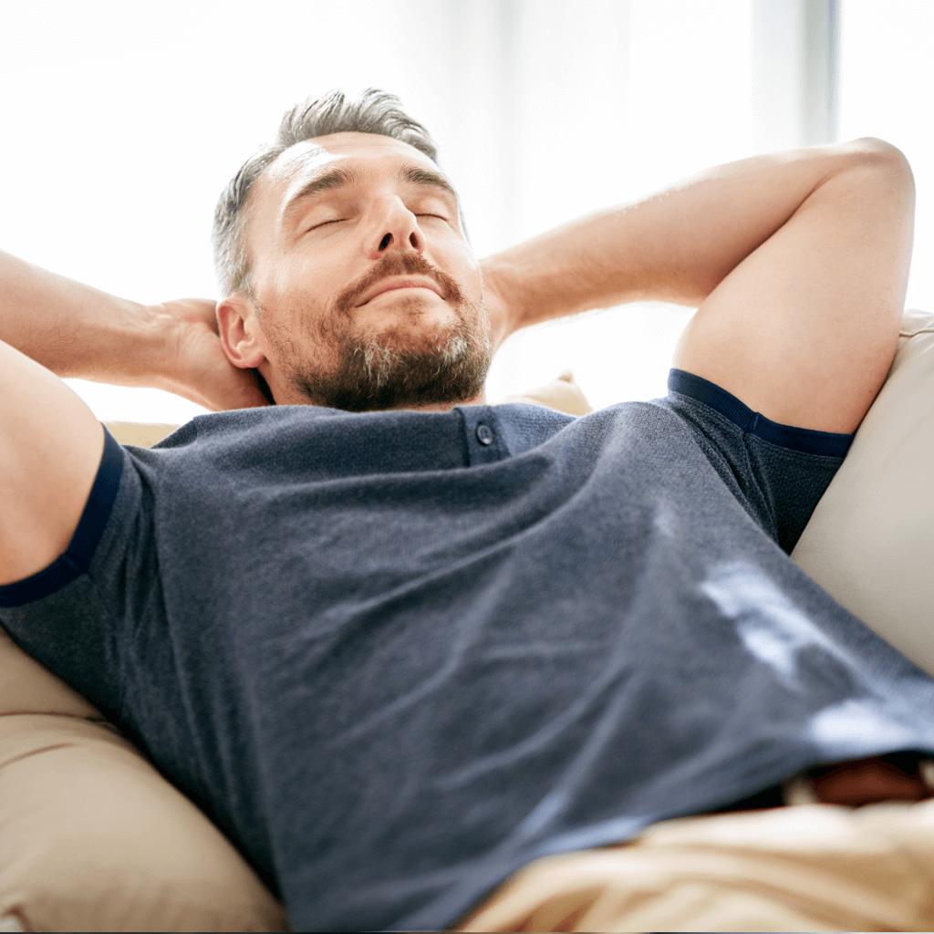 Mann liegt entspannt auf einer Couch